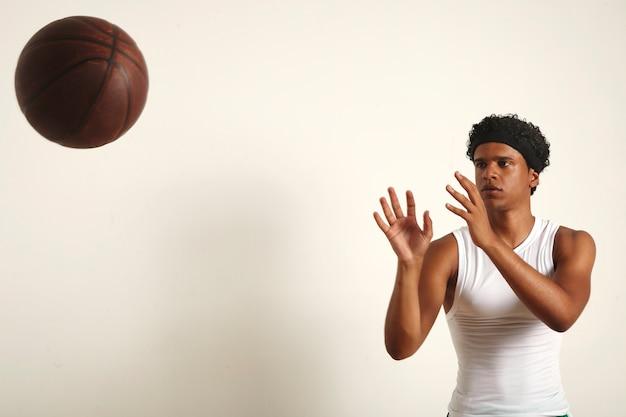 Starker ernsthafter schwarzer athlet mit einem afro im einfachen weißen ärmellosen hemd, das einen dunkelbraunen vintage-basketball auf weiß wirft Kostenlose Fotos