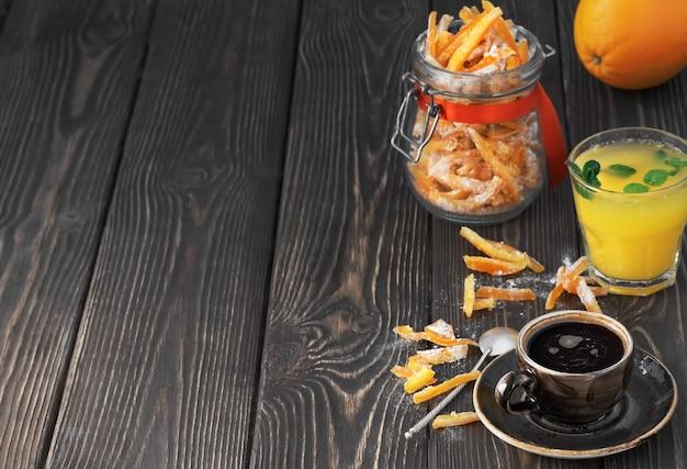 Starker espresso, frisch gepresster orangensaft mit minzblättern und kandierten früchten im glas Premium Fotos