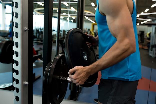 Starker mann, der gewichtsplatten aufnimmt Premium Fotos