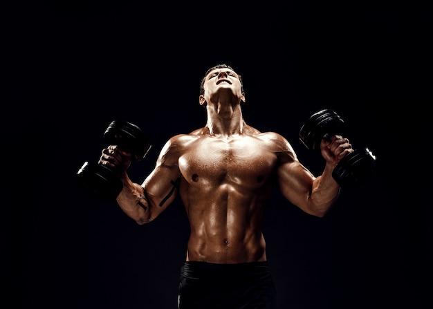 Starker muskulöser mann, der übung mit dummköpfen tut Premium Fotos