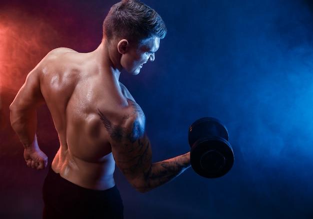 Starker muskulöser mann, der übung mit dummkopf tut Premium Fotos