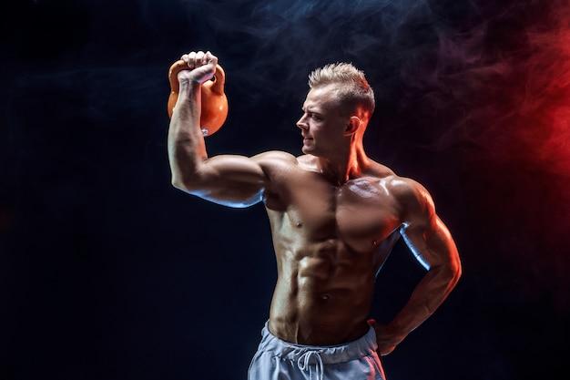 Starker muskulöser mann, der übung mit kettlebell tut Premium Fotos
