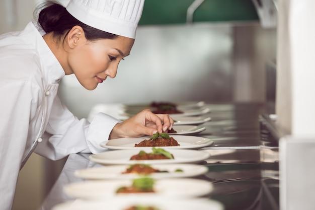 Starker weiblicher chef, der lebensmittel in der küche schmückt Premium Fotos