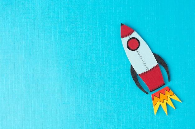 Start-up unternehmen . einkommen, gehalt steigern oder steigern. gezeichnete rakete auf buntem blauem hintergrund. copyspace. Premium Fotos