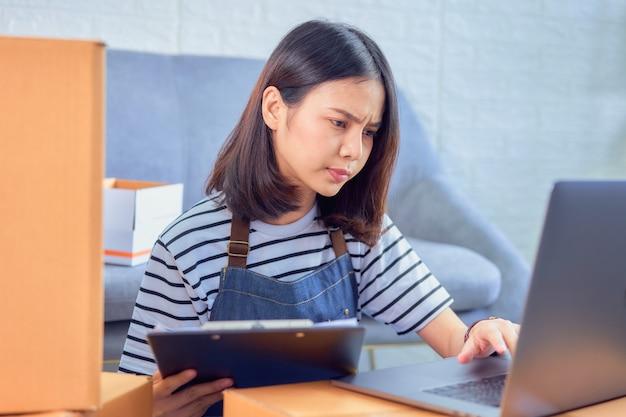 Startkleingewerbe, junger asiatineigentümer überprüfen den kundenauftrag vom computer, verkäufer bereitet den lieferungskasten vor. Premium Fotos