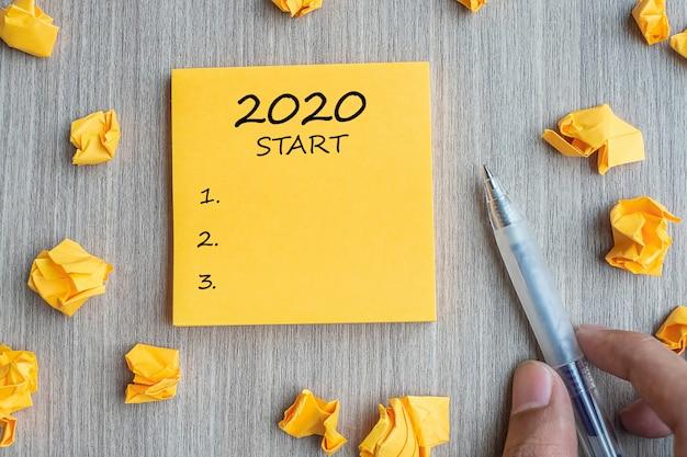 Startliste 2020 auf gelber note mit zerknitterten papieren und einem stift Premium Fotos