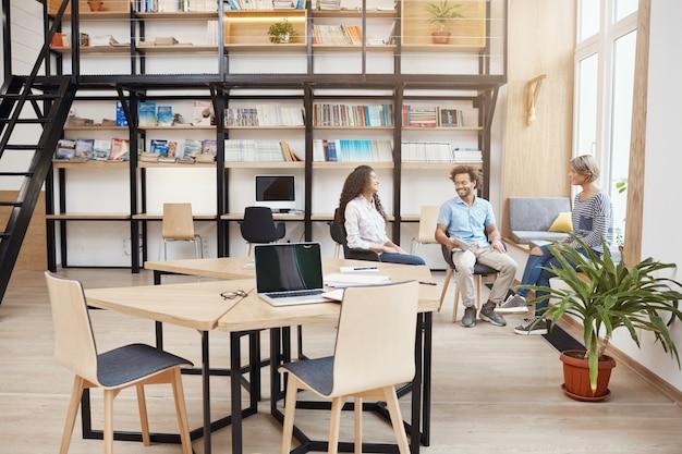 Startup-, business-, teamwork-konzept. gruppe von jungen leuten aus der perspektive beim treffen in einer großen modernen bibliothek, die über die gewinne des letzten projekts sprechen, durch papiere schauen, lächeln und produktive zeit haben Kostenlose Fotos