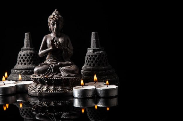 Statue von buddha sitzend in der meditation, kerzen, mit schwarzem exemplarplatz Premium Fotos