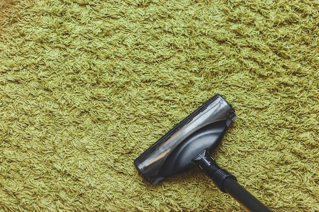 Staubsaugerbürste auf grünem teppich, draufsicht. Premium Fotos