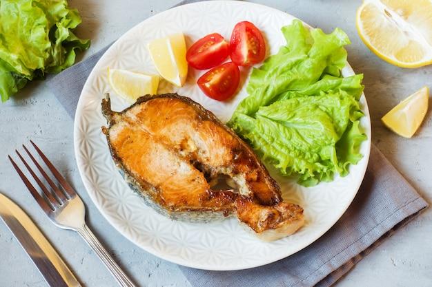 Steak gebackene lachsfische auf einer platte mit frischgemüse. Premium Fotos