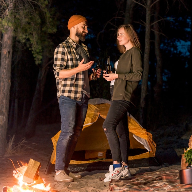 Stehende paare, die durch campingzelt sprechen Kostenlose Fotos