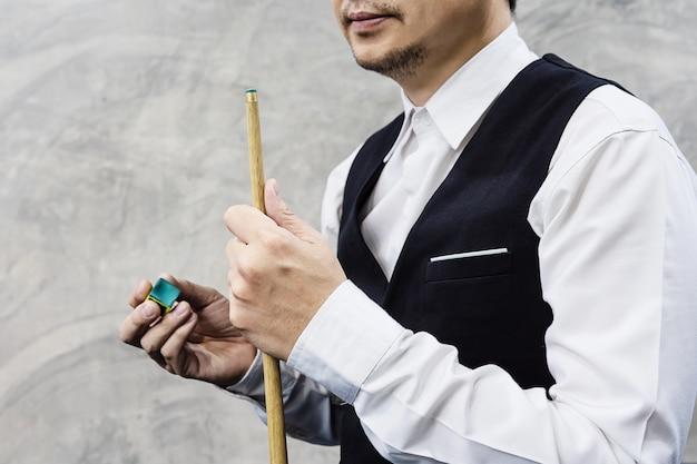 Stehende wartezeit des snookerspielers hält seinen stichwortstock und -kreide Kostenlose Fotos