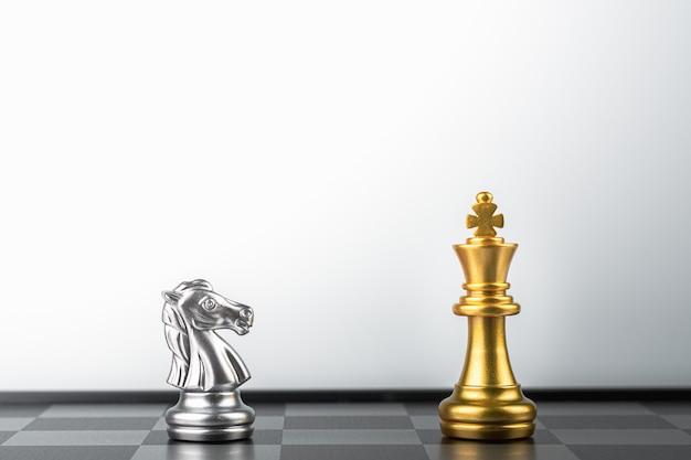 Stehender goldener königsschach trifft auf silberne ritterfeinde. Premium Fotos