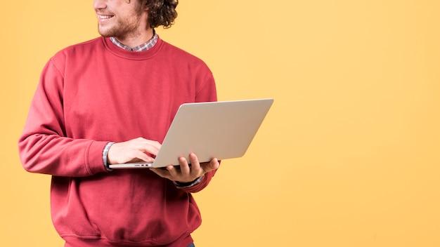 Stehender mann, der laptop verwendet Kostenlose Fotos
