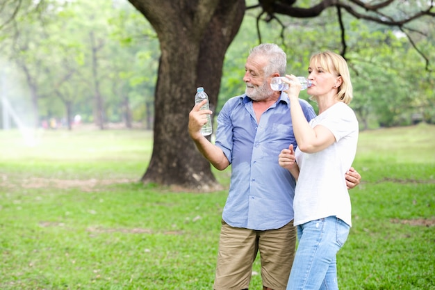 Stehendes trinkwasser des älteren paares des portraits am park Premium Fotos