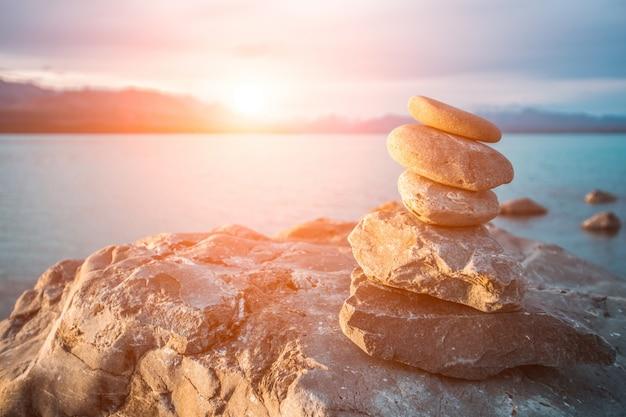 Steine im meer bei sonnenuntergang gestapelt Kostenlose Fotos