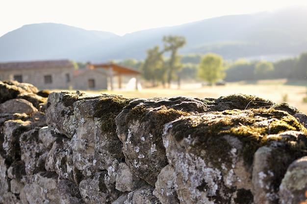 Steinmauer mit moos und unscharfem häuschen Premium Fotos