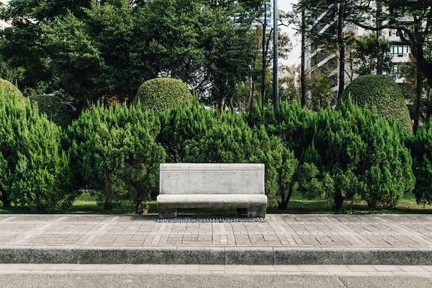 Steinsitz im park mit kiefern im hintergrund Premium Fotos