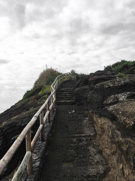 Steintreppe zur spitze des hügels mit holzgeländer unter bewölktem grauem himmel nach dem regen Kostenlose Fotos
