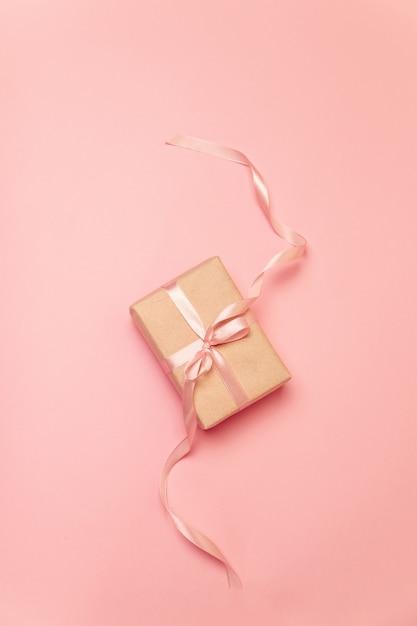Stellen sie geschenkbox mit rosa pastellbogenband auf rosa segeltuch her Premium Fotos