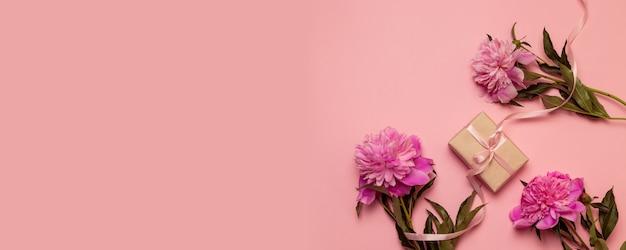 Stellen sie geschenkbox mit rosa pastellbogenband und pfingstrosenblumen auf rosa segeltuch her Premium Fotos