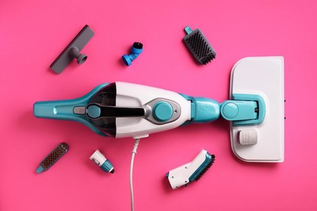 Stellen sie mit modernen berufsdampfreinigern auf rosa hintergrund ein. reinigungsservice-konzept Premium Fotos