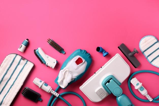 Stellen sie mit modernen berufsdampfreinigern auf rosa hintergrund ein. Premium Fotos