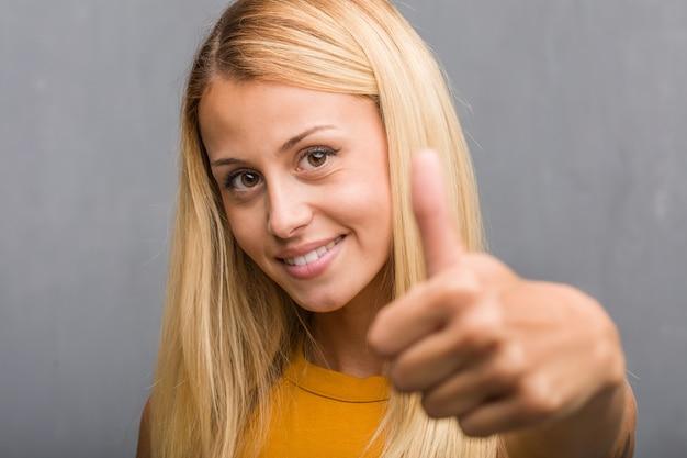 Stellen sie nahaufnahme, portrait einer natürlichen jungen blonden frau gegenüber, die nett und aufgeregt ist, oben lächeln und oben lächeln Premium Fotos