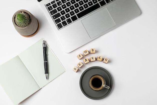 Stellenrecherchenwort auf stempeln, kaffeetasse, tastatur, stift, notizblock, arbeitslosigkeit auf grau Premium Fotos