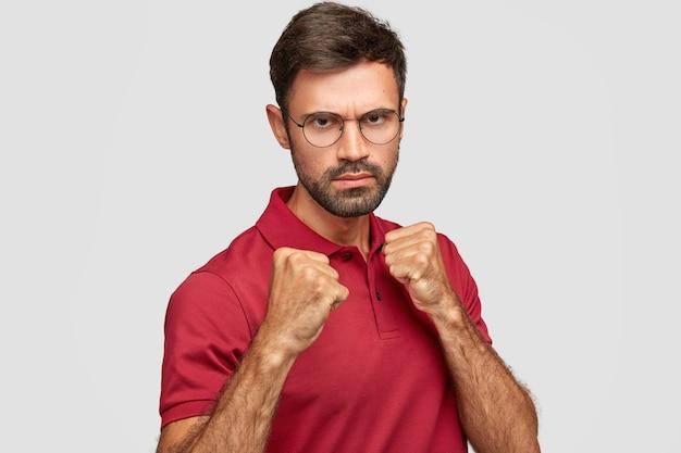 Stern ernst unrasierten mann hält hände in fäusten, bereit, mit konkurrenten zu kämpfen, schaut unter augenbrauen, hat missfallenen ausdruck, gekleidet in lässiges rotes t-shirt, steht gegen weiße wand drinnen Kostenlose Fotos