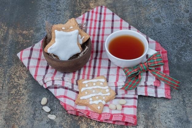 Sternförmige lebkuchen und tasse tee auf tischdecke. hochwertiges foto Kostenlose Fotos