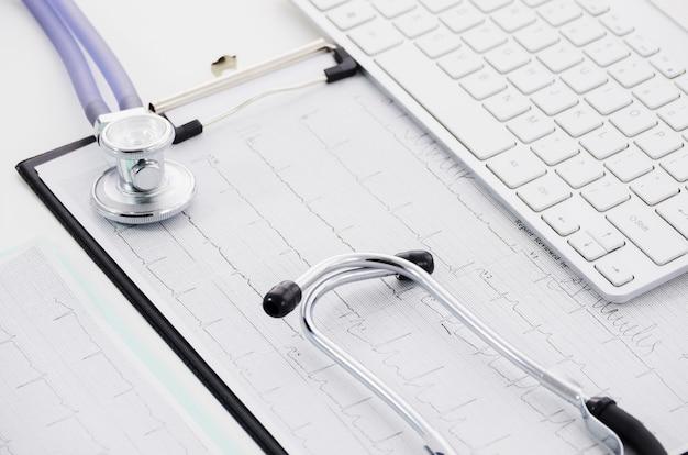 Stethoskop auf ecg papierdiagramm und laptop auf weißem hintergrund Kostenlose Fotos