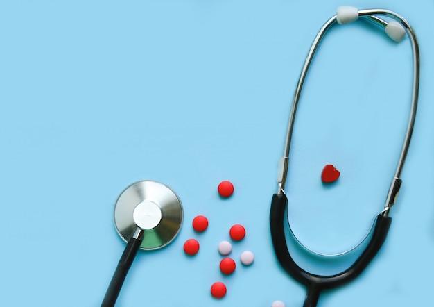 Stethoskop auf einem blauen hintergrund mit pillen und einem roten herzen Premium Fotos