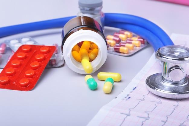 Stethoskop auf rx-rezept mit verschiedenen pillen liegen. gesundes leben oder versicherungskonzept. Premium Fotos