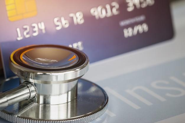 Stethoskop auf verspotten herauf kreditkarte mit zahl auf karteninhaber im krankenhausschreibtisch. krankenversicherung Premium Fotos