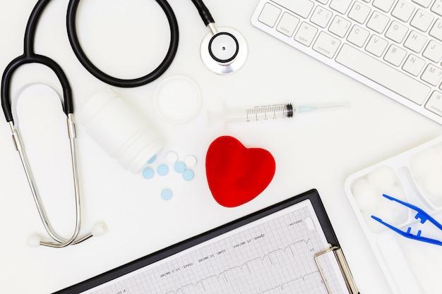 Stethoskop, draufsicht der schreibtischtabelle doktors, über ansichtdoktorarbeitswerkzeugen auf weißem, arztschreibtischkonzept. Premium Fotos