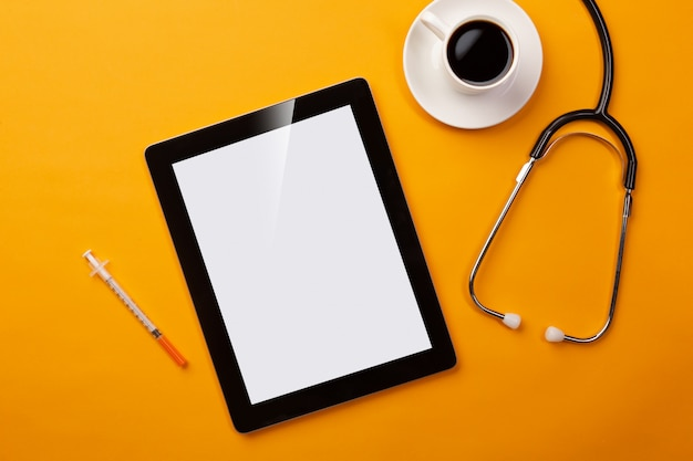 Stethoskop im doktorschreibtisch mit digitaler tablette, kaffeetasse, spritze und pillen Premium Fotos