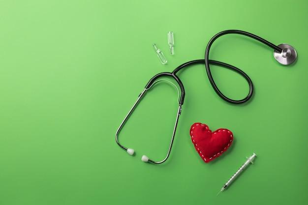 Stethoskop im doktorschreibtisch mit herzen, spritze und ampullen Premium Fotos