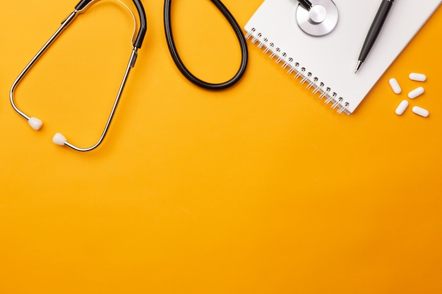 Stethoskop in doktorschreibtisch mit notizbuch und pillen, draufsicht Premium Fotos