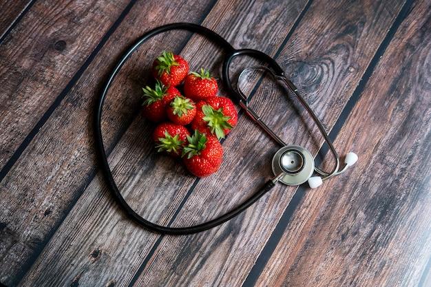 Stethoskop mit erdbeeren auf holztisch. medizin und gesundheitswesen konzeptionell. Kostenlose Fotos
