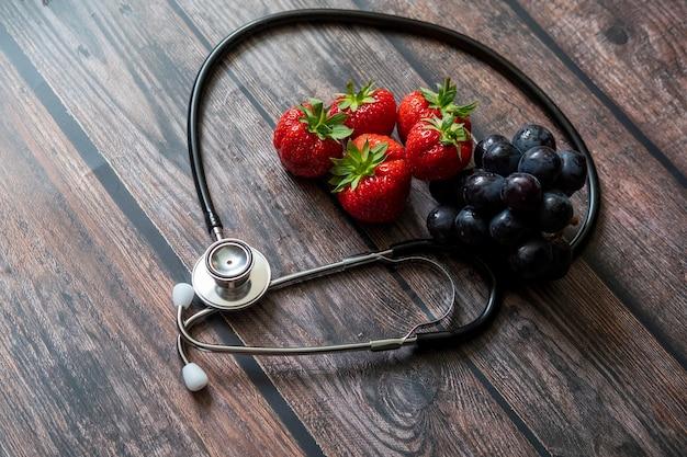 Stethoskop mit erdbeeren und schwarzer kernloser traube auf holztisch. Kostenlose Fotos