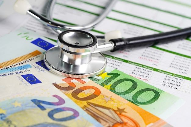 Stethoskop mit euro-banknoten auf spreedsheet-papier Premium Fotos