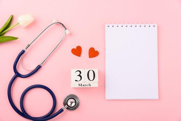 Stethoskop, papiernotiz, kalender, rote herzen und tulpenblume Premium Fotos
