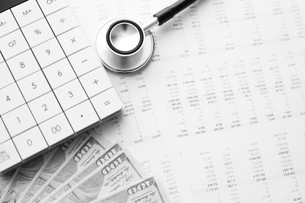 Stethoskop, taschenrechner und geld für medizinische daten. konzept der gesundheitskosten oder der krankenversicherung Premium Fotos