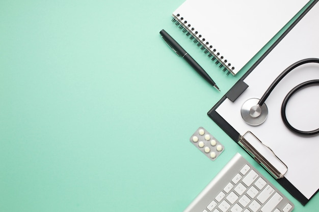 Stethoskop und blisterpackung der pille mit büroartikel über grünem hintergrund Kostenlose Fotos