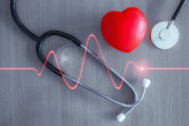 Stethoskop und rotes herz mit glühender roter herzwelle. Premium Fotos