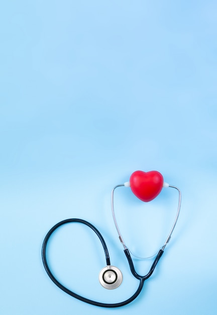 Stethoskop und rotes herz über kopf auf hellblauem hintergrund mit platz für text Premium Fotos