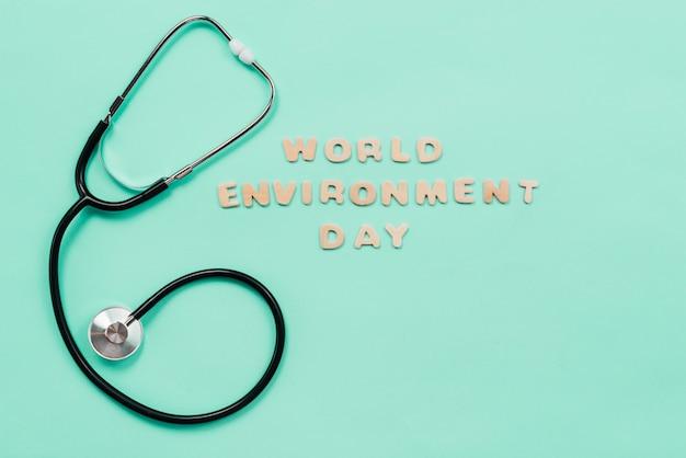 Stethoskop- und wortumwelttag unterzeichnen auf grünem hintergrund Kostenlose Fotos