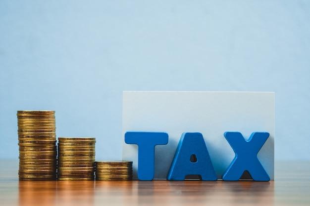 Steuer-alphabet mit stapel der münze und der visitenkarte Premium Fotos