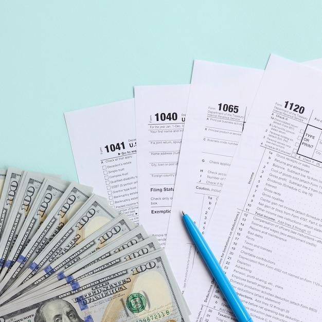 Steuerformulare liegen nahe hundert dollarscheinen und blauem stift auf einem hellblauen hintergrund. einkommensteuerrückerstattung Premium Fotos